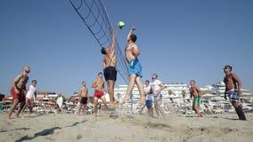 Jeunes amis de groupe jouant le volleyball sur la plage Photos stock
