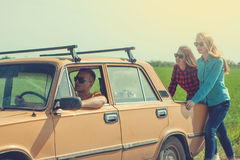 Jeunes amis de hippie sur le voyage par la route sur une voiture Image libre de droits
