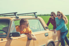 Jeunes amis de hippie sur le voyage par la route sur une voiture Images libres de droits