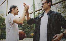 Jeunes amis de mâle adulte jouant le basket-ball en parc Photos stock