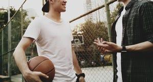 Jeunes amis de mâle adulte jouant le basket-ball en parc Image stock
