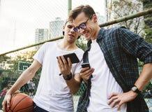 Jeunes amis de mâle adulte sur le terrain de basket utilisant le smartphon Photo stock