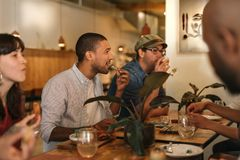 Jeunes amis de sourire appréciant le dîner ensemble dans un Bistro à la mode Photo stock