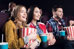 jeunes amis de sourire avec le film de observation de maïs éclaté Image stock