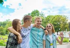Jeunes amis de sourire heureux marchant en parc Photographie stock