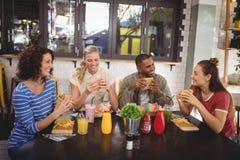 Jeunes amis de sourire mangeant de la nourriture tout en se reposant au café Photos stock