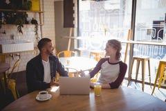 Jeunes amis de sourire parlant tout en se reposant avec l'ordinateur portable au café Photographie stock libre de droits