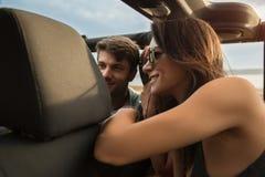 Jeunes amis de sourire parlant tout en se reposant dans une voiture Images libres de droits