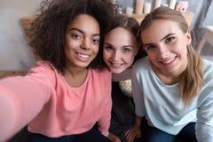 Jeunes amis de sourire prenant le selfie dans la chambre à coucher à la maison Photographie stock