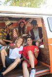 Jeunes amis de sourire s'asseyant dans le camping-car Image libre de droits