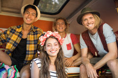 Jeunes amis de sourire s'asseyant ensemble dans le camping-car Images libres de droits