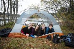 Jeunes amis de sourire se situant dans la tente sur au bord du lac Photographie stock libre de droits