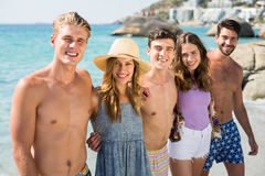 Jeunes amis de sourire se tenant à la plage Images libres de droits