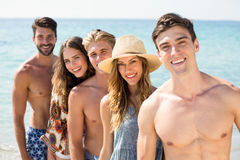 Jeunes amis de sourire se tenant contre la mer Image libre de droits