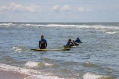 Jeunes amis de surfer dans des wetsuits marchant hors de la mer Image libre de droits