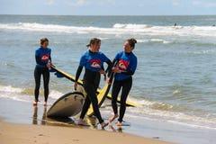 Jeunes amis de surfer dans des wetsuits marchant le long du rivage Images stock