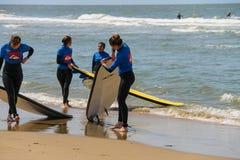 Jeunes amis de surfer dans des wetsuits marchant le long du rivage Photos stock