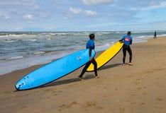 Jeunes amis de surfer dans des wetsuits marchant le long du rivage Image stock