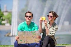 Jeunes amis de touristes voyageant en vacances dans le sourire de l'Europe heureux Famille caucasienne avec la carte de ville à l Photographie stock libre de droits