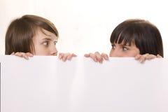 Jeunes amis derrière un panneau-réclame Photographie stock