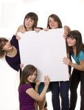 Jeunes amis derrière un panneau-réclame Photographie stock libre de droits