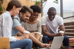 Jeunes amis divers heureux regardant l'ordinateur portable sur la terrasse de café image libre de droits