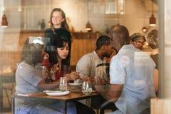 Jeunes amis divers mangeant ensemble à une table de Bistros Images stock