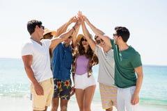 Jeunes amis donnant la haute cinq tout en se tenant à la plage Image stock