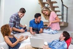 Jeunes amis employant des technologies modernes sur le sofa Photo libre de droits