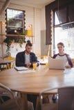 Jeunes amis employant des technologies tout en se reposant au café Images libres de droits