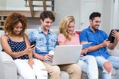 Jeunes amis employant des technologies tout en se reposant sur le sofa Photographie stock