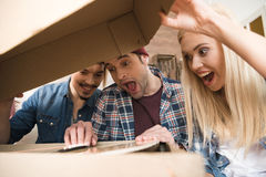 Jeunes amis enthousiastes ouvrant la boîte avec la guitare Images stock