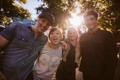 Jeunes amis enthousiastes se tenant ensemble au parc d'attractions Photographie stock