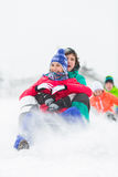 Jeunes amis enthousiastes sledding dans la neige Photographie stock libre de droits