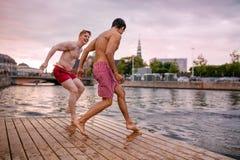 Jeunes amis environ à sauter dans le lac Images stock
