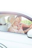 Jeunes amis féminins appréciant le voyage par la route dans la voiture le jour ensoleillé Photos libres de droits