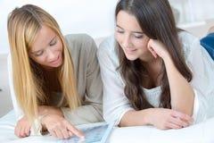 Jeunes amis féminins appréciant lisant le magazine ensemble Photographie stock libre de droits