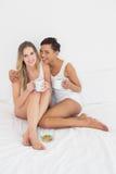 Jeunes amis féminins avec des tasses de café dans le lit Image stock