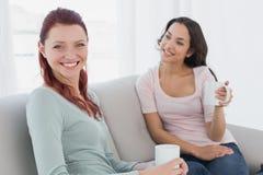Jeunes amis féminins avec des tasses de café se reposant à la maison Photos stock
