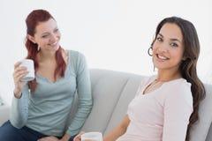 Jeunes amis féminins avec des tasses de café se reposant à la maison Photo stock