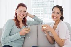 Jeunes amis féminins avec des verres de vin à la maison Images stock