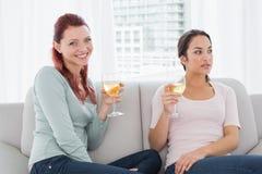 Jeunes amis féminins avec des verres de vin à la maison Photo stock