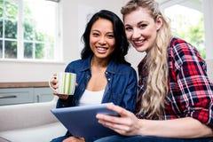 Jeunes amis féminins avec la tasse et le comprimé numérique sur le sofa Photo libre de droits
