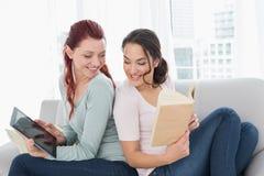 Jeunes amis féminins avec le comprimé numérique et le livre à la maison Photo stock