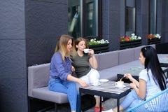 Jeunes amis féminins buvant du café et s'asseyant au café Image libre de droits