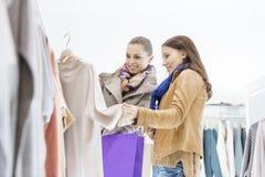 Jeunes amis féminins choisissant le chandail dans le magasin Photo stock