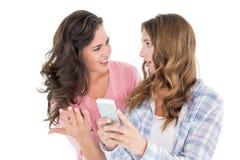 Jeunes amis féminins choqués avec le téléphone portable Photos stock