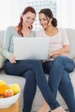 Jeunes amis féminins décontractés à l'aide de l'ordinateur portable à la maison Images stock