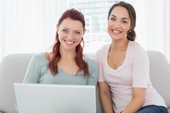 Jeunes amis féminins décontractés à l'aide de l'ordinateur portable à la maison Images libres de droits
