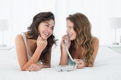 Jeunes amis féminins décontractés à l'aide du téléphone dans le lit Photographie stock libre de droits